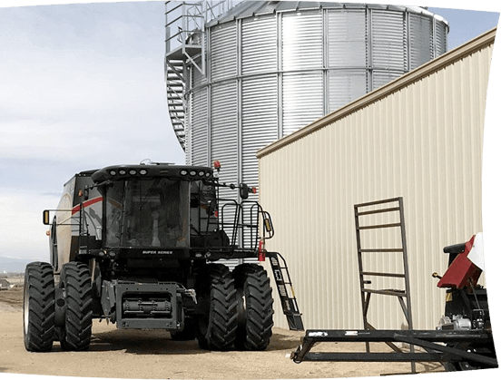 tractor combine in front of silo at hemp farm